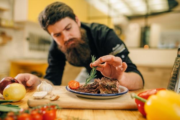 Шеф-повар-мужчина украшает жареные кусочки мяса зеленью в тарелке, кухня на заднем плане. человек готовит говядину с овощами на столешнице