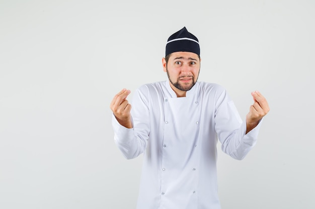 Male chef explaining something in white uniform and looking helpless , front view.