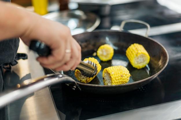 鍋でトウモロコシの穂軸を揚げる男性シェフ