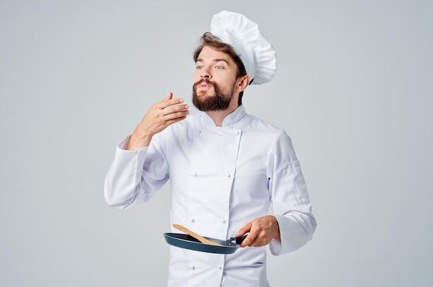 男性シェフのフライパンを手で調理する食品グルメ明るい背景。高品質の写真