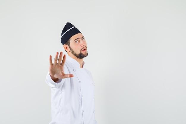 Cuoco maschio che fa gesti come rifiutare qualcosa in uniforme bianca e sembra calmo. vista frontale.