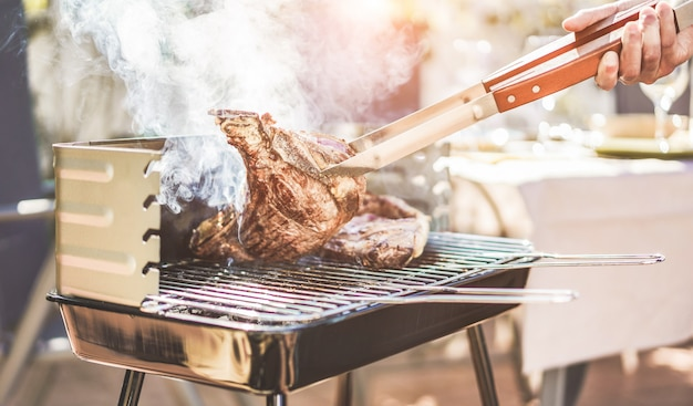 Male chef grill t-bone steak at barbecue dinner outdoor - man cooking meat for a family bbq meal outside in backyard garden