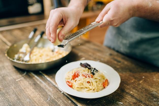 男性シェフの手が新鮮な調理されたフェットチーネとプレートにチーズをすりおろし、木製のキッチンテーブルの上でパンします。自家製パスタの準備プロセス。伝統的なイタリア料理