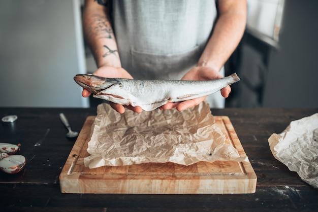 Мужские руки шеф-повара держат сырую рыбу над деревянной разделочной доской. приготовление морепродуктов. свежие морепродукты