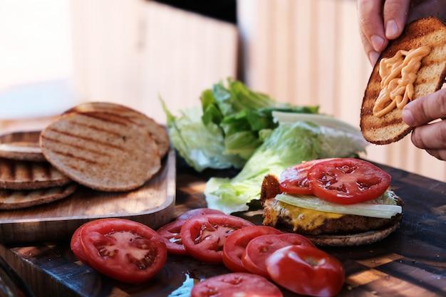 Male chef hands preparing burgers