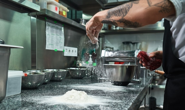 Male chef hands with black tattoos pouring flour on kitchen table. food concept