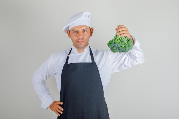 Male chef in hat, apron and uniform holding broccoli and putting hand on waist