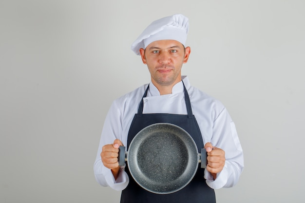 Male chef in hat, apron and uniform holding empty pan and looking glad