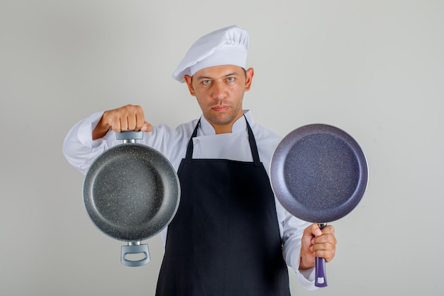 Male chef in hat, apron and uniform holding empty pans