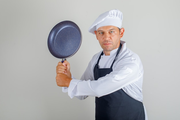 Male chef in hat, apron and uniform holding frying pan while having fun