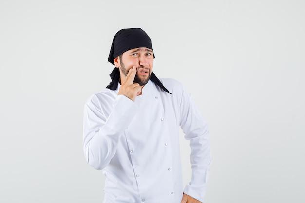 남자 요리사는 하얀 제복을 입은 고통스러운 이빨을 가지고 있고 불편해 보이는 전면 전망을 가지고 있습니다.