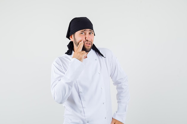 Male chef having painful tooth in white uniform and looking uncomfortable , front view.