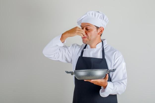 悪い皿を押しながら帽子、エプロン、制服を着た鼻を閉じる男性シェフ