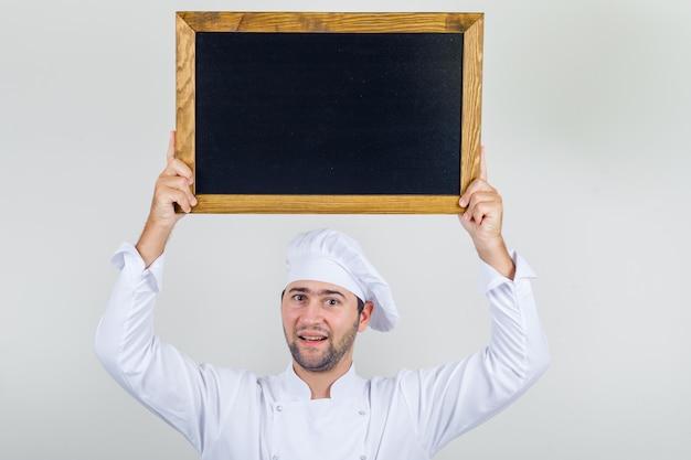 Cuoco unico maschio che tiene lavagna sopra la testa in uniforme bianca e guardando positivo.