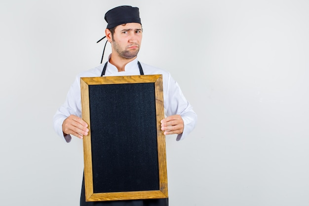 Male chef holding blackboard in uniform, apron and looking discontented. front view.