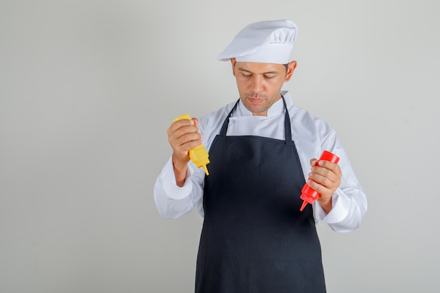 Male chef holding bottles of ketchup and mustard in hat, apron and uniform