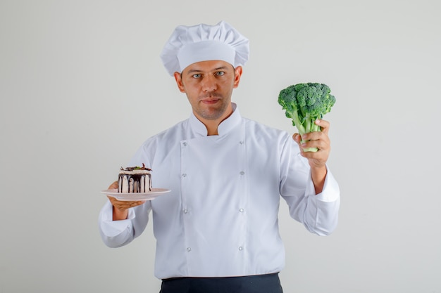 Male chef holding broccoli and dessert cake in uniform, apron and hat