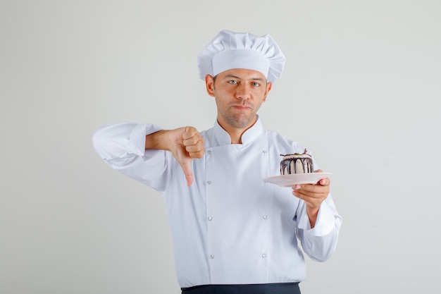 Мужской шеф-повар держа торт и показывая большой палец руки вниз в форме, переднике и шляпе вид спереди.