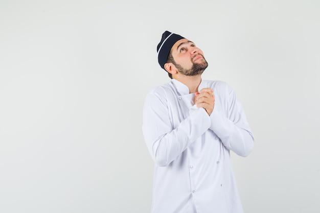 Cuoco unico maschio che tiene le mani giunte in gesto di preghiera in uniforme bianca e guardando speranzoso, vista frontale.