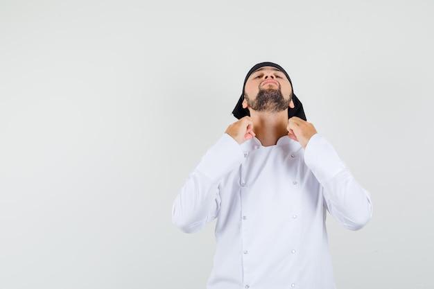 흰색 유니폼을 입고 머리를 뒤로 구부리고 잘생긴 전면 전망을 바라보면서 칼라를 잡고 있는 남성 요리사.