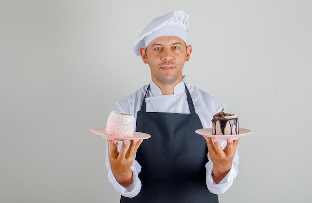 Мужской шеф-повар держит десерт торт в тарелках в шляпе, фартук и униформа