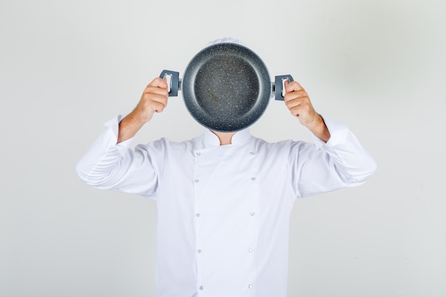 Male chef holding empty pan over his face in white uniform