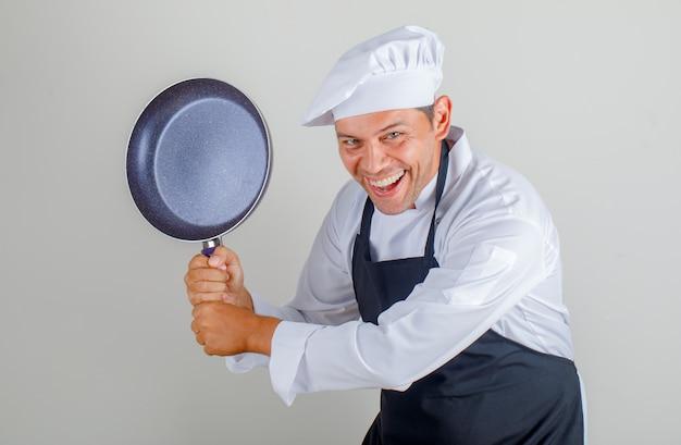 帽子、エプロン、ユニフォームを楽しんでいる間、フライパンを押しながら面白い探している男性シェフ