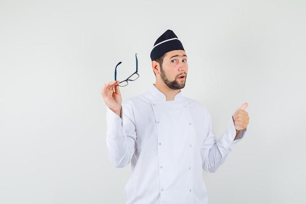 흰색 유니폼을 다시 가리키고 의아해하는 동안 안경을 들고 남성 요리사. 전면보기.