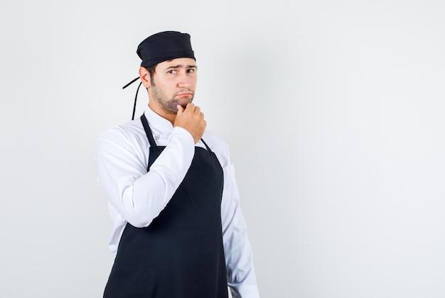 Chef maschio tenendo la mano sul mento in uniforme, grembiule e guardando pensieroso. vista frontale.