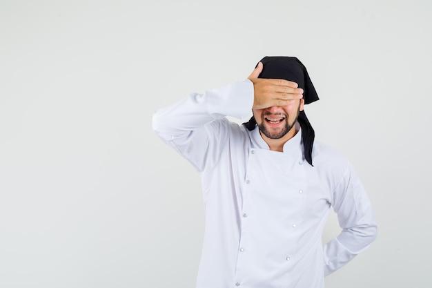 Cuoco unico maschio che tiene la mano sugli occhi in uniforme bianca e sembra desideroso, vista frontale.