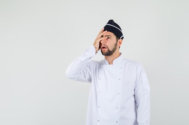 Chef maschio tenendo la mano sul viso in uniforme bianca e guardando preoccupato, vista frontale.