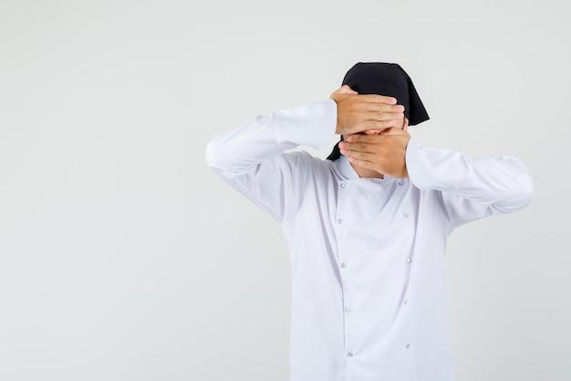 남자 요리사는 흰색 제복을 입고 눈과 입에 손을 잡고 까마귀를 찾고 있습니다. 전면보기.