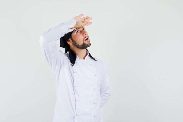 남자 요리사는 흰색 유니폼을 입고 이마에 손을 잡고 사려깊은 표정을 짓고 있습니다. 전면보기.