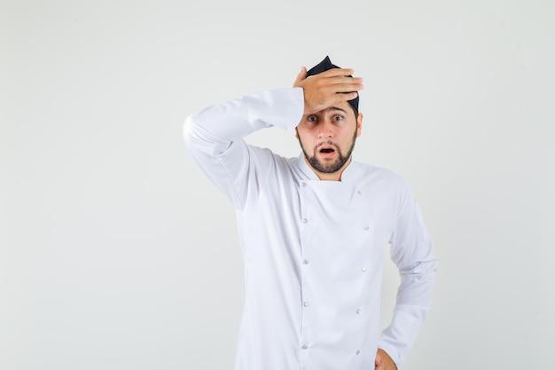 흰색 제복을 입은 남자 요리사가 이마에 손을 잡고 놀란 표정을 짓고 있습니다.