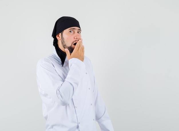 Cuoco unico maschio che tiene la mano sulla bocca aperta in uniforme bianca e sembra sorpreso. vista frontale.