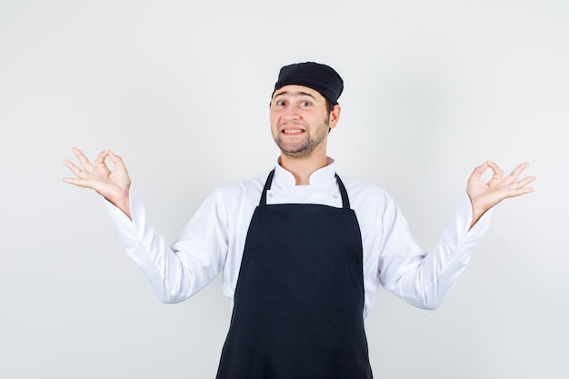 Male chef holding hands in yoga gesture in uniform, apron and looking cheerful , front view.
