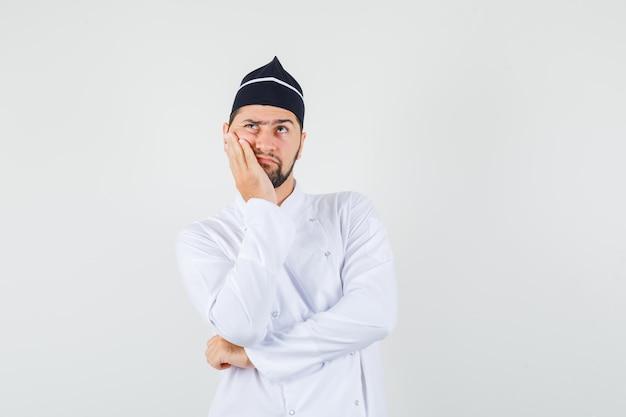Cuoco unico maschio che tiene il palmo sulla guancia in uniforme bianca e sembra pensieroso. vista frontale.