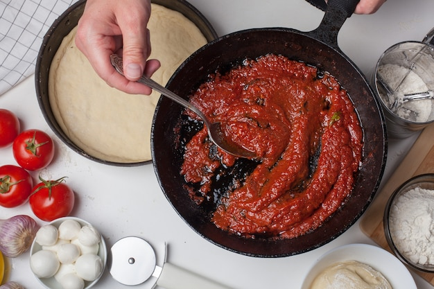 Male chef holding a pan with tomato sauce.