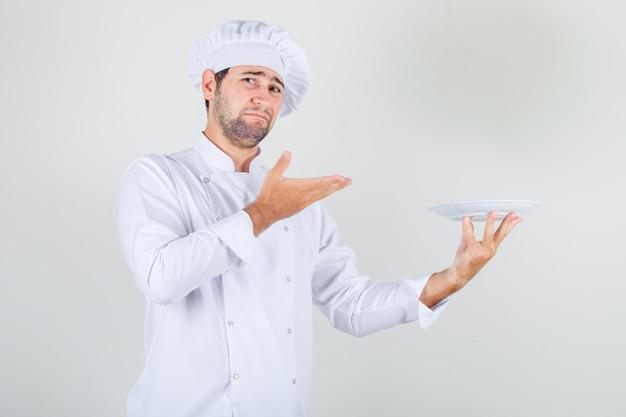男性シェフが白い制服を着たプレートを保持し、不機嫌そうに見えます。