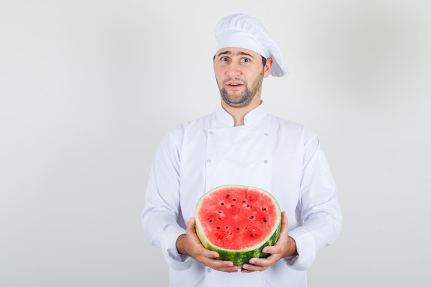 Шеф-повар-мужчина держит нарезанный арбуз в белой форме и выглядит позитивно.