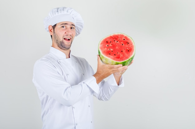 Male chef holding sliced watermelon in white uniform and looking happy.