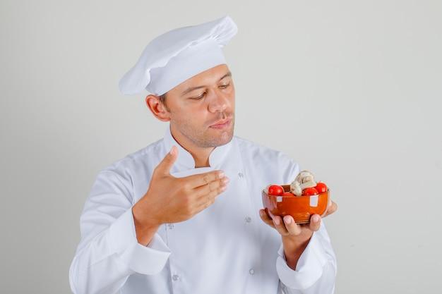 帽子と制服のボウルにトマトとキノコを保持している男性のシェフ