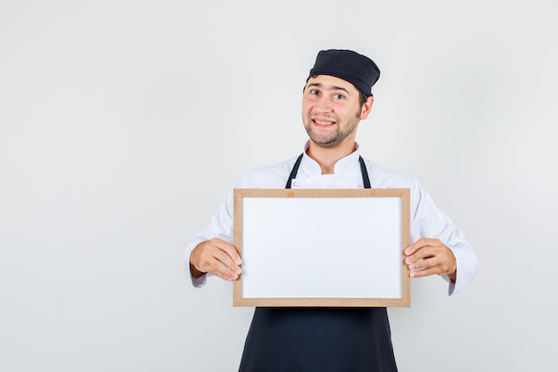 Male chef holding white board in uniform, apron and looking cheerful. front view.
