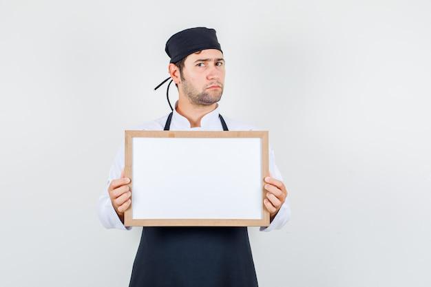 Cuoco unico maschio che tiene scheda bianca in uniforme, grembiule e guardando sconvolto. vista frontale.