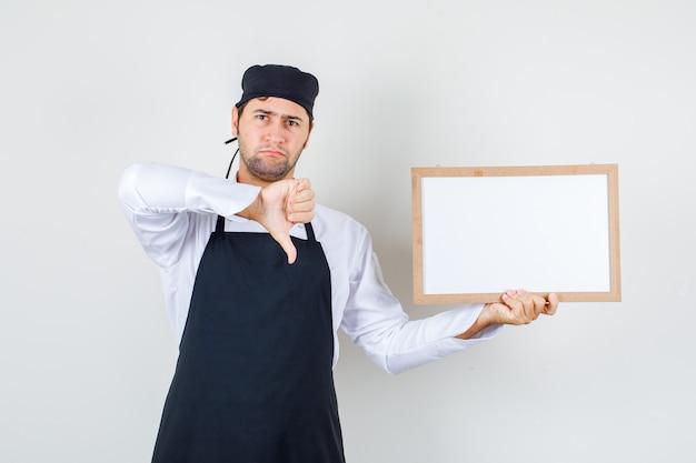 Cuoco unico maschio che tiene bordo bianco con il pollice giù in uniforme, grembiule e sguardo cupo. vista frontale.