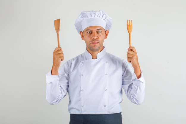 Male chef holding wooden kitchen utensils in uniform, apron and hat