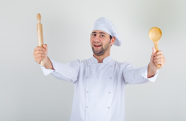 Male chef holding wooden spoon and rolling-pin in white uniform and looking cheerful