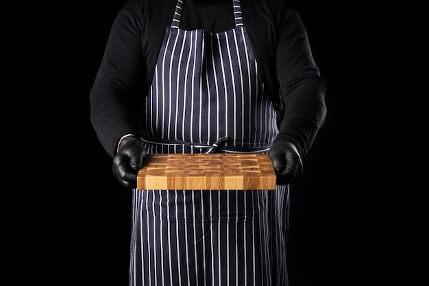 Шеф-повар в полосатом синем фартуке и черной одежде стоит на черном фоне и держит в руке прямоугольную деревянную разделочную доску для кухни.