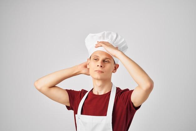 Шеф-повар-мужчина в белом фартуке шляпы работает светлом фоне