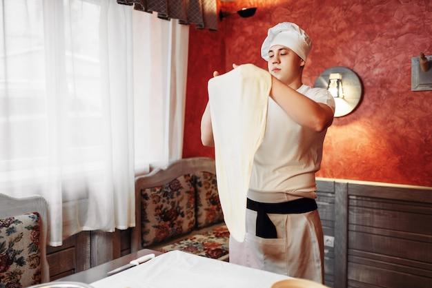 キッチンで生地を作るエプロンと帽子の男性シェフ。自家製のリンゴのシュトルーデル料理、甘いデザートの準備